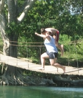 two crazy people jumping off the Hammock Bridge in San Ignacio Belize