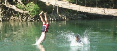 two crazy people hitting the water after jumping off the Hammock Bridge in San Ignacio Belize